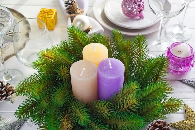 Decoración festiva en la mesa de navidad con velas, linterna, vajilla.