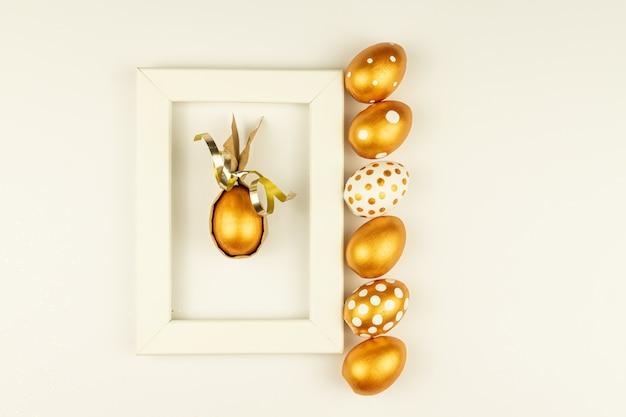 Decoración festiva de pascua. vista superior de huevos de pascua coloreados con pintura dorada y marco de fotos de maqueta vacío. varios diseños de puntos. fondo blanco.