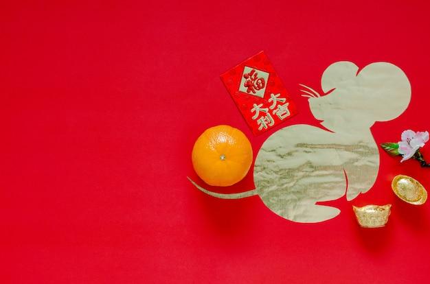 Decoración del festival del año nuevo chino sobre fondo rojo que corta en forma de rata en papel dorado.