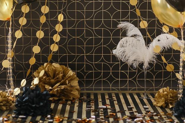 Decoracion de fiesta. decoración dorada sobre fondo negro con globos.