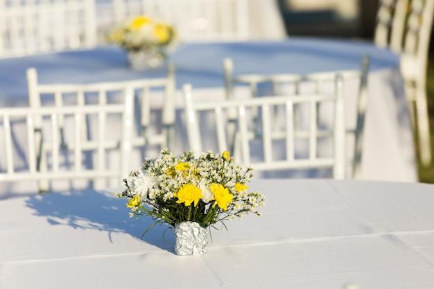 Decoración de flores en mesa blanca al aire libre en recepción de boda.