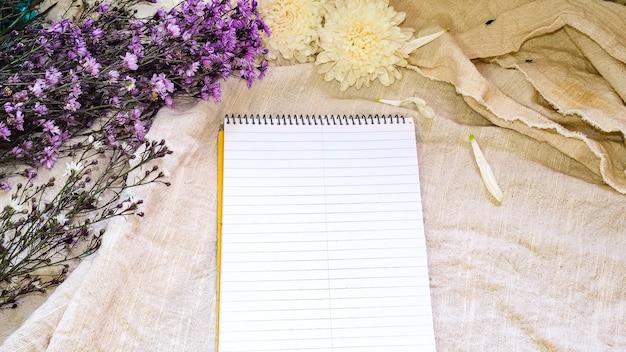 Decoración de flores y papel en blanco. tarjeta de felicitación en un blanco natural; fondo de lino. vista superior. copie el espacio.