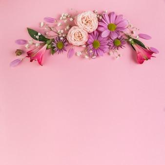 Decoración de flores sobre fondo rosa.