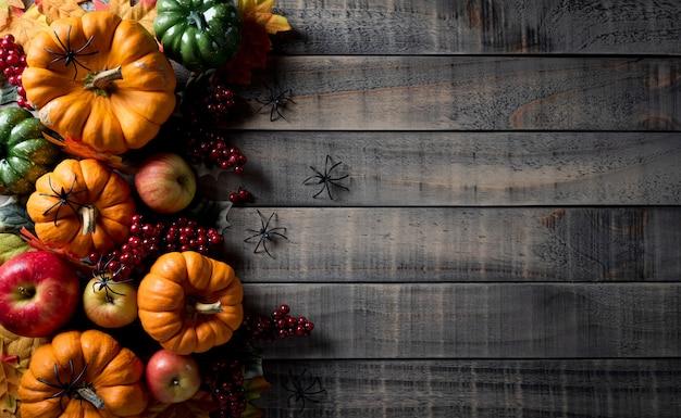 Decoración de fondo otoñal de calabazas, bayas, manzanas rojas y hojas