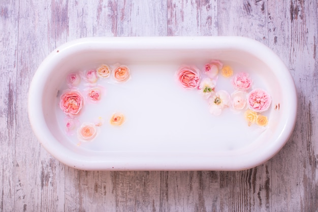 Decoración fotográfica de un baño blanco antiguo para bebé con rosas frescas
