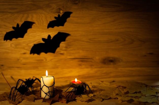 Decoración de halloween con araña en la web y velas sobre fondo de madera