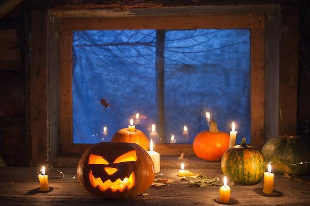 Decoración de halloween, calabazas y jack-o-lantern junto a velas encendidas