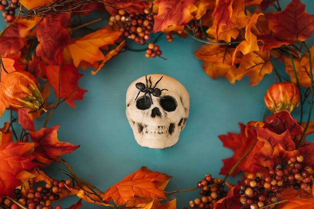 Decoración de halloween con cráneo y hojas de otoño