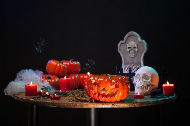 Decoración de halloween diferente sentado en una mesa de madera. calabaza aterradora. cráneo espeluznante.
