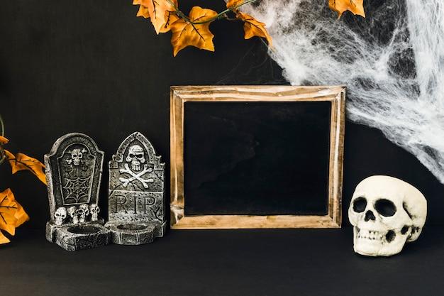 Decoración de halloween con pizarra y objetos espantosos