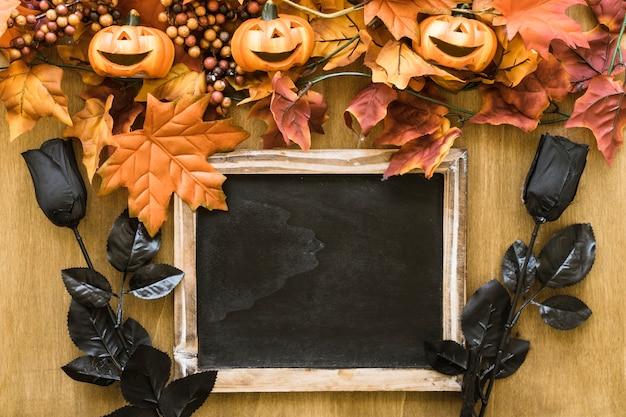 Decoración de halloween con pizarra y rosas negras
