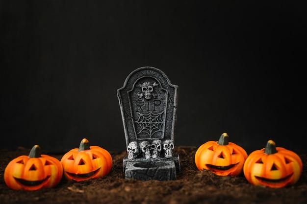 Decoración de halloween con tumba y calabazas