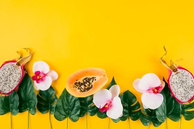 Decoración hecha con papaya; frutas de dragón; orquídeas y hojas artificiales sobre fondo amarillo.