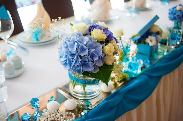 Decoración hermosa de los ramos en la tabla de la boda en un restaurante