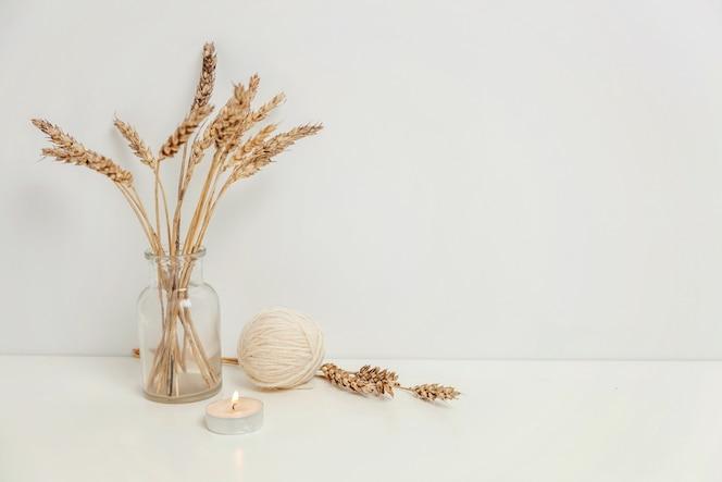 Decoración del hogar ecológica natural con ramo de centeno silvestre en florero de vidrio cerca de una pared blanca