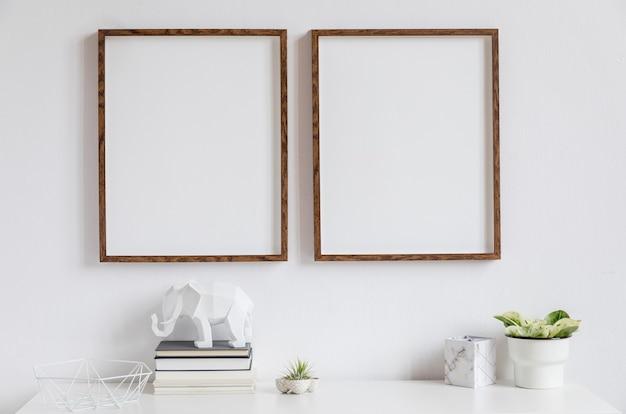 Decoración del hogar minimalista de interior con dos marcos de fotos de madera marrón en el estante blanco con libros, hermosa planta en maceta elegante y accesorios para el hogar. pared blanca.