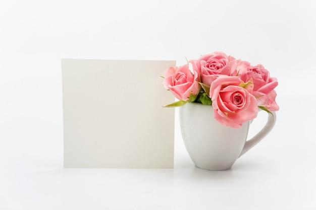Decoración del hogar, tarjeta vacía y taza con rosas.