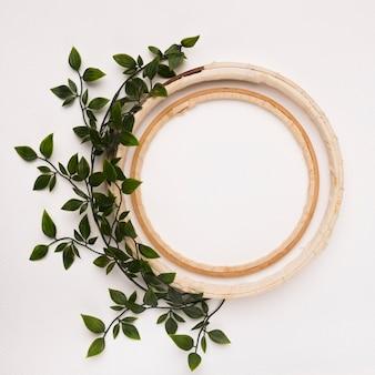 Decoración de hojas con círculos de madera vacíos sobre fondo blanco.