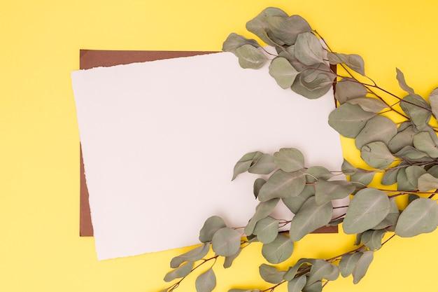 Decoración de hojas secas y tarjeta vacía.