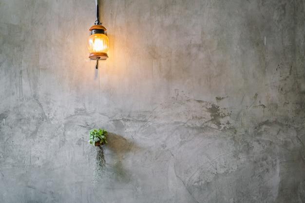 Decoración de la iluminación del vintage con la planta sobre la pared del cemento.