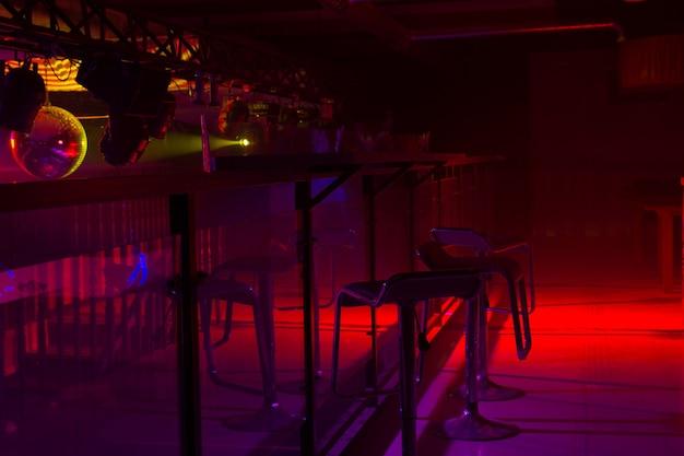 Decoración interior de bar moderno y colorida iluminación estroboscópica roja y púrpura que ilumina una fila de elegantes taburetes en un mostrador