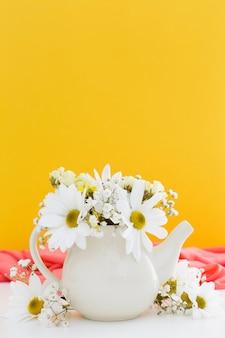 Decoración con margaritas blancas y fondo amarillo.
