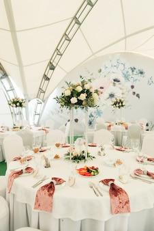 Decoración de mesas decoradas con flores frescas para una cena festiva.