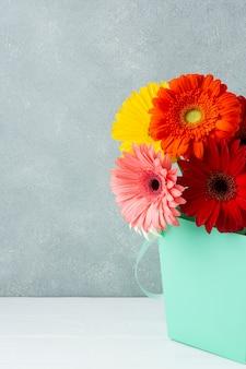 Decoración minimalista con flores de gerbera en un cubo.