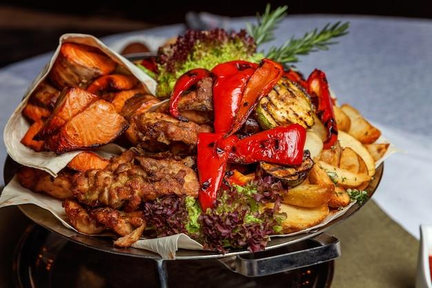 Decoración mixta de carne a la parrilla, verduras fritas y filetes de salmón a la parrilla en un plato caliente