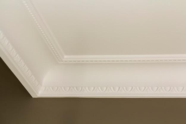 Decoración de molduras blancas ornamentales en el techo del detalle de primer plano de la sala blanca. renovación interior y concepto de construcción.