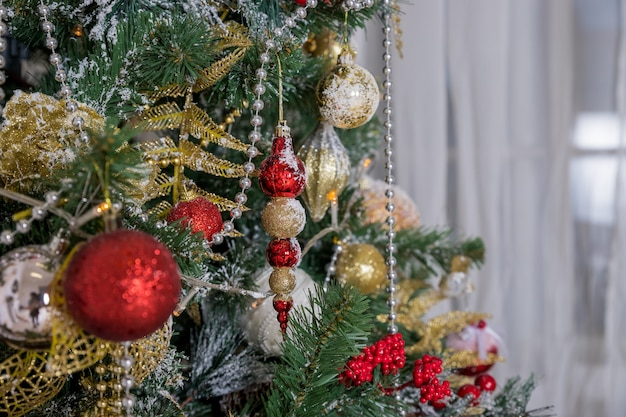 Decoración de navidad y año nuevo. diseño de arte de vacaciones de invierno con adornos navideños. primer hermoso del árbol de navidad adornado con la estrella del oro, baya del acebo, oropel. árbol de navidad decorado.
