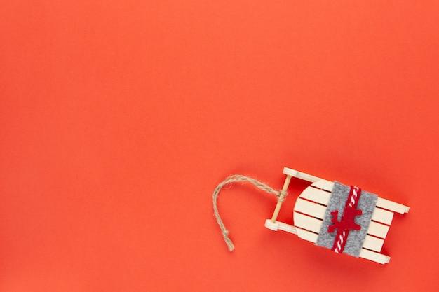 Decoración de navidad, árbol de juguete, trineo de madera con ciervos sobre fondo rojo con copyspace. festivo, año nuevo