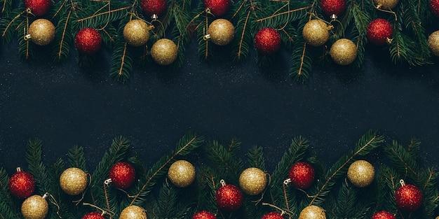 Decoración de navidad con árbol de navidad y bolas sobre fondo negro.