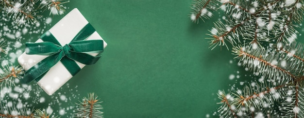 Decoración de navidad con árbol de navidad y regalo blanco sobre fondo verde. feliz tarjeta de navidad vacaciones de invierno.