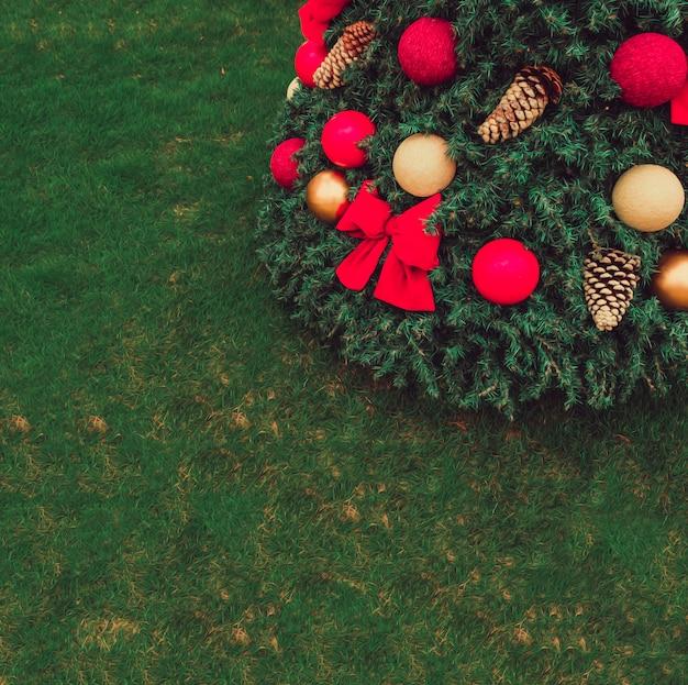 Decoración de navidad con árbol de navidad sobre hierba.