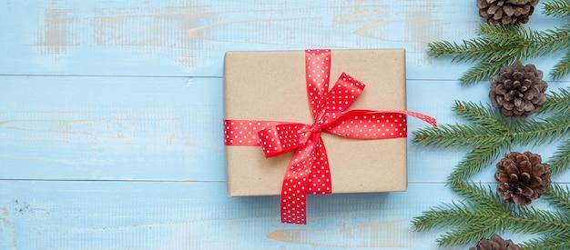 Decoración de navidad, caja de regalo y ramas de árboles de pino sobre fondo de madera