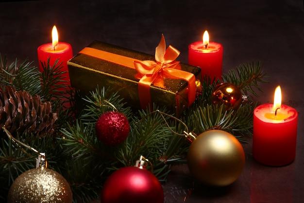 Decoración de navidad con cajas de regalo, velas rojas, árbol de navidad y bolas de colores.