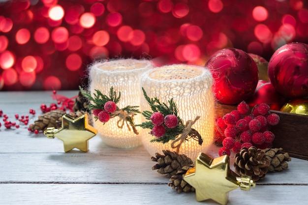 Decoración de navidad decorado con velas, bayas rojas, conos y estrellas doradas en la mesa de madera blanca, rojo bokeh de fondo