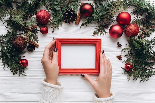 Decoración de navidad en el fondo de madera blanco. mujer que sostiene un marco de fotos.