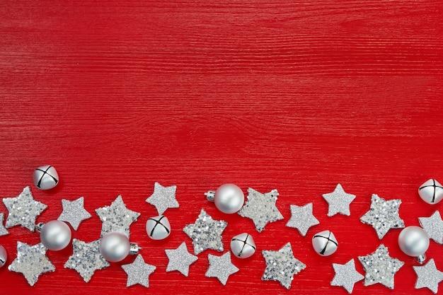 Decoración de navidad plata sobre fondo rojo. endecha plana. vista superior, copyspace. fondo rojo de navidad con estrellas y campanas.