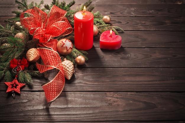 Decoración de navidad roja y dorada con velas encendidas sobre fondo de madera
