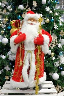 Decoración de navidad santa claus en pleno crecimiento se levanta contra el fondo del árbol de navidad. composición navideña