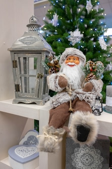 Decoración de navidad santa claus sentado cerca de un árbol de navidad con una linterna para velas. composición navideña. juguete de navidad santa claus.