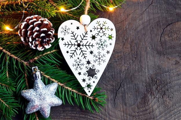 Decoración navideña con abeto, guirnalda de luz y corazón blanco sobre madera vieja