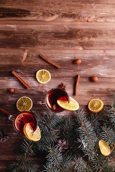 Decoración navideña y año nuevo. dos copas de vino caliente con naranjas.
