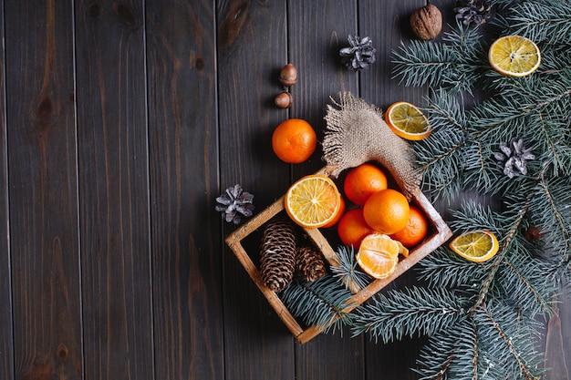 Decoración navideña y año nuevo. naranjas, conos y ramas de árboles de navidad.