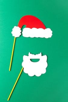 Decoración navideña, barba blanca y sombrero rojo de papá noel en palos sobre fondo verde