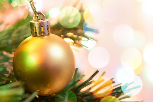 Decoración navideña. bolas de oro colgantes en ramas de pino guirnalda de árboles de navidad y adornos sobre bokeh abstracto con espacio de copia