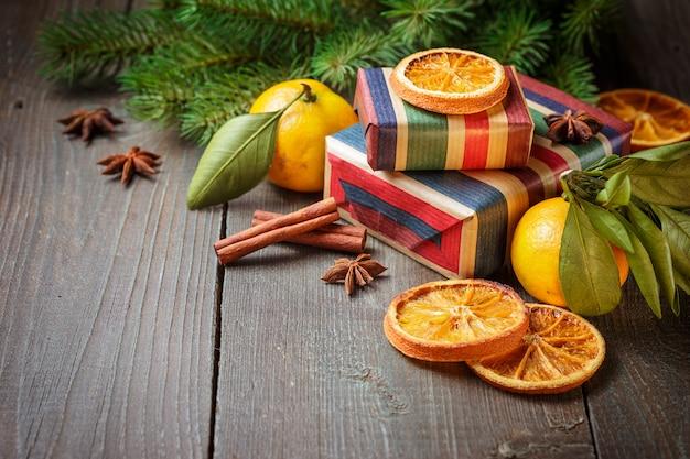 Decoración navideña con cajas de regalo y mandarinas