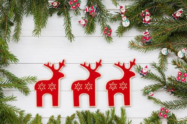 Decoración navideña con ciervo sobre fondo blanco de madera